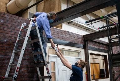 A woman hands an item to Steve Krahnke, who is on a ladder.