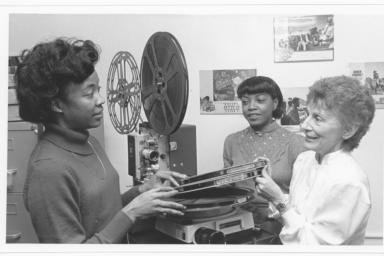 Three women looking at reels of film