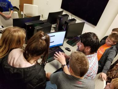 Andrew Behringer shows Stalker Elementary School students a computer in the game design lab