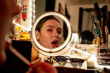 A woman looks in the mirror as she applies makeup.