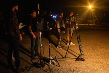 Four students using cameras on tripods