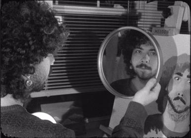 Ty Vinson looks into a mirror while painting a portrait of himself