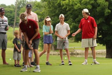 A man putts on a golf course as six other people watch.