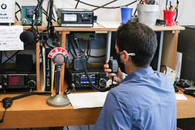 Jayson Deese speaks into an amateur radio receiver.