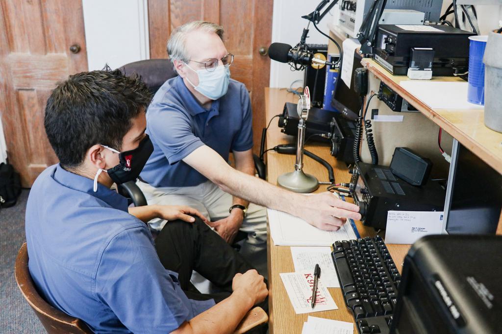 Matt Pierce and Jayson Deese operate amateur radio equipment.