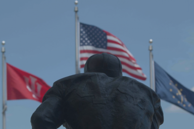 A statue of George Taliaferro is seen with the Indiana, IU and United States flags