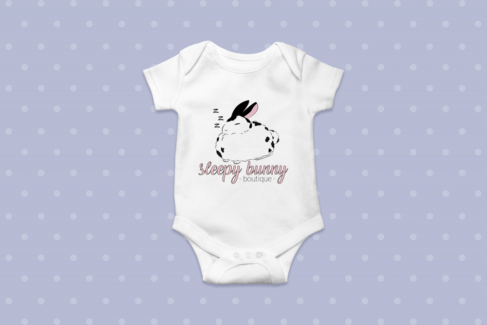 "A onesie with an illustration of a sleeping rabbit with the words ""Sleepy Bunny Boutique."""