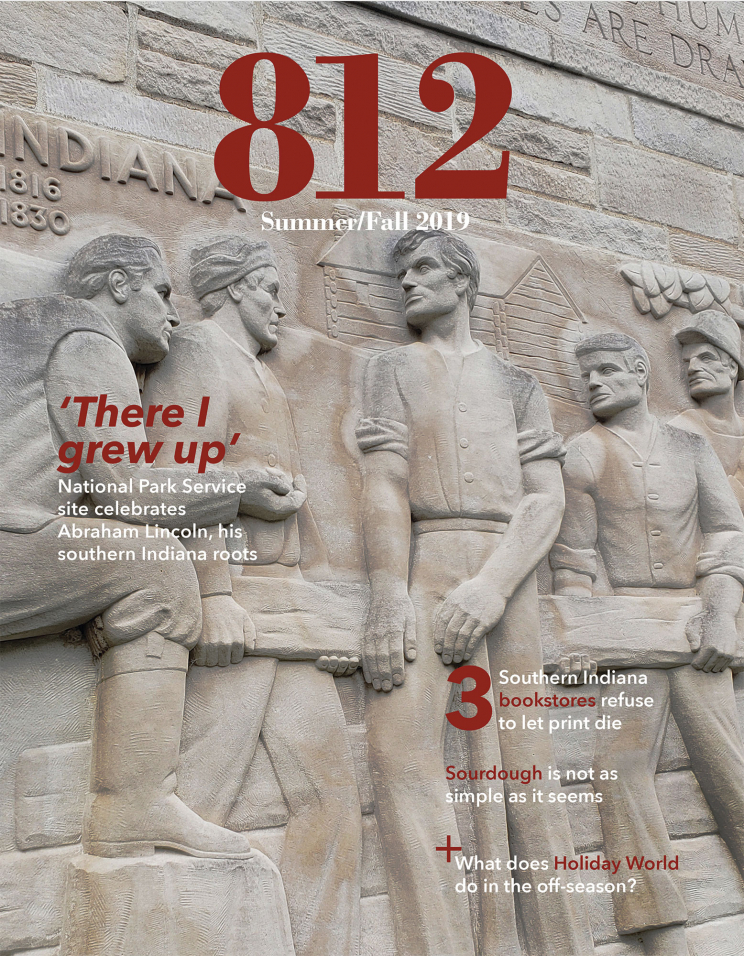 "The cover of 812 magazine Summer/Fall 2019 issue. It shows a scene of Abraham Lincoln carrying a wooden log with four other men, carved into limestone. The headlines are: ""There I grew up: National Park Service site celebrates Abraham Lincoln, his southern Indiana roots""; ""3 Southern Indiana bookstores refuse to let print die""; ""Sourdough is not as simple as it seems""; ""+What does Holiday World do in the off season?"""