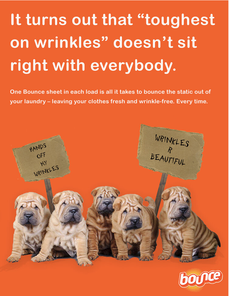 "An advertisement for Bounce dryer sheets. It depicts five wrinkly Shar-Pei puppies holding picket signs that say ""Hands off my wrinkles"" and ""Wrinkles R beautiful."" The text says: ""It turns out that 'toughest on wrinkles' doesn't sit right with everybody. One Bounce sheet in each load is all it takes ot bounce the static out of your laundry -- leaving your clothes fresh and wrinkle-free. Every time."""