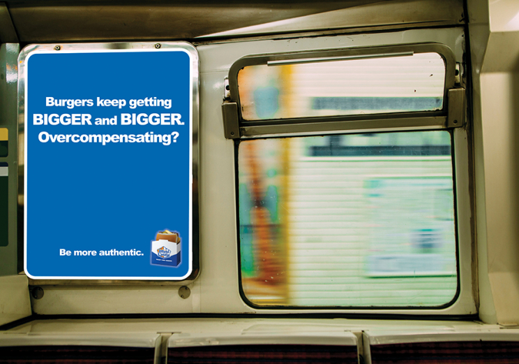 """An advertisement for White Castle on a subway train. It says: """"Burgers keep getting BIGGER and BIGGER. Overcompensating? Be more authentic."""" There is a small White Castle hamburger in the bottom right corner."""