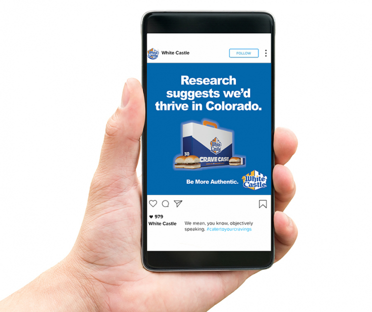 """An iPhone displaying an Instagram ad for White Castle. It depcits a case of White Castle hamburgers with the text: """"Research suggests we'd thrive in Colorado. Be More Authentic."""""""