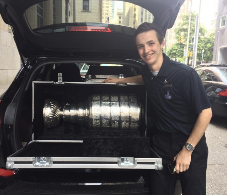 Fuller showing off the Stanley Cup in the trunk of a car.