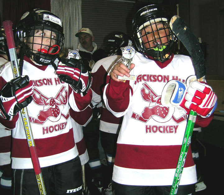 Two boys, dressed in hockey gear, holding up trophies