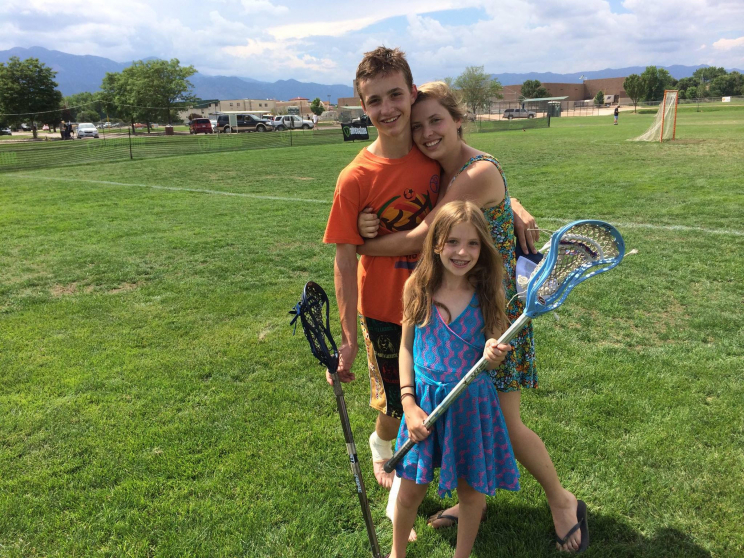 Fuller with two girls on a lacrosse field