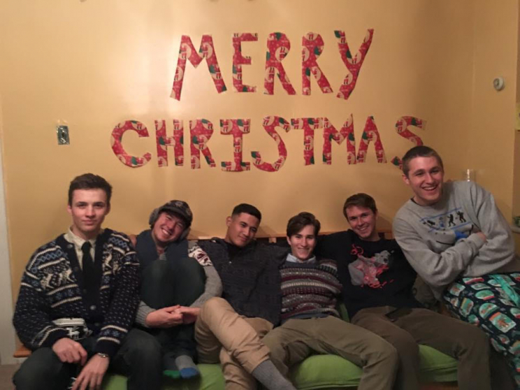 """Six men sitting on a couch under the words """"Merry Christmas"""""""
