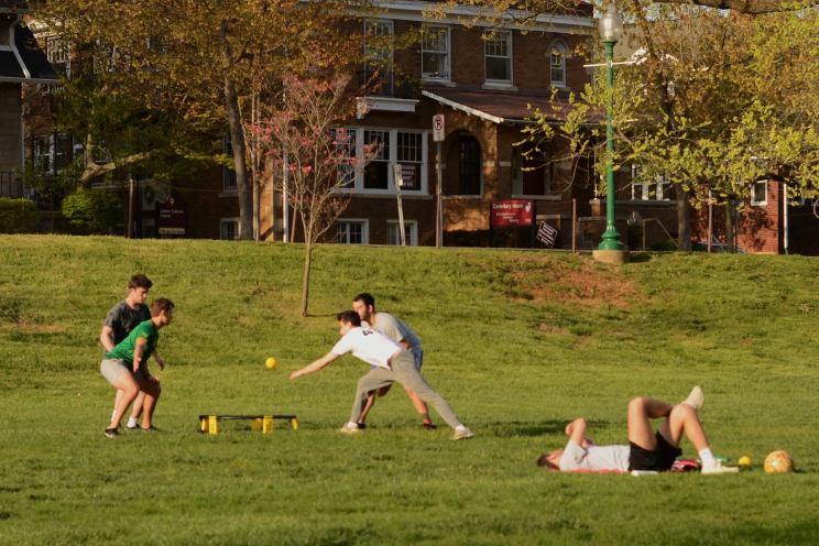 Four students playing a ball game in Dunn Meadow.